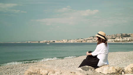 Young woman in hat sitting by the beach in the resort town. Woman in white blouse sitting by the water, looking at sea and dreaming on background of city buildings