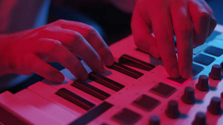 Male hands recording music, playing electronic keyboard, midi keys on the table with neon lights. Closeup of male hands composing music in night using midi controller Stock fotó