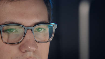 Closeup of man eyes in eyeglasses in front of the computer, gimbal pan shot left to right, concentrated look. Young man sitting working alone at night