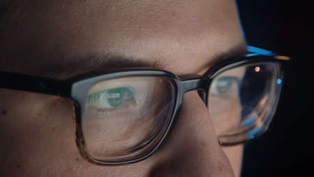 Macro shot of man eyes in eyeglasses in front of the computer, gimbal shot in home office, concentrated look. Young man sitting at home working alone at night