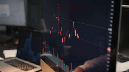 Computer screen with stock market changes, scrolling and analysing numbers. Man and computer display, no face, stock market with green and red market changes Stock fotó