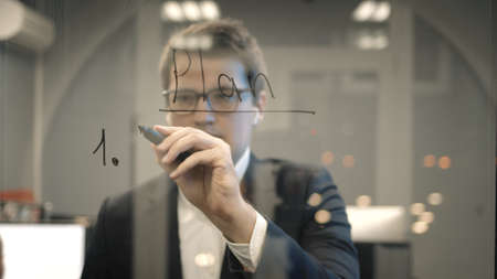 Young businessman in suit writing word plan on the transparent glass wall in the office. Front view of man in eyeglasses writing plans on glass in the office room