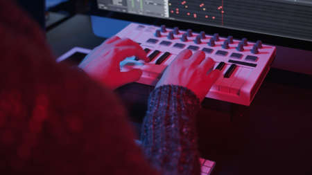 Recording music notes, playing electronic keyboard, midi keys in music sequencer. Hands and midi controller on the table with neon lights, man composing music in night Stock fotó