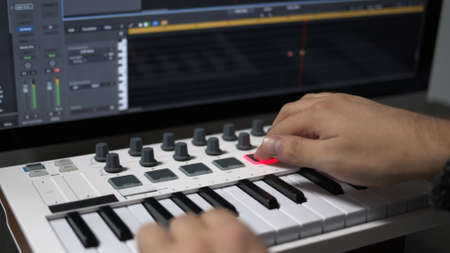 Male hands recording music, playing electronic keyboard, midi keys on the table. Closeup of male hands composing music in sequencer using midi keyboard with keys and pads
