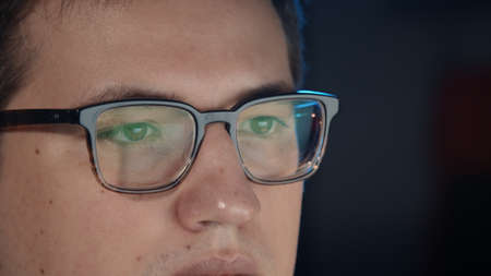 Closeup of man eyes in eyeglasses in front of the computer, gimbal pan shot right to left, concentrated look. Young man manager working alone at night, hard work Stock fotó