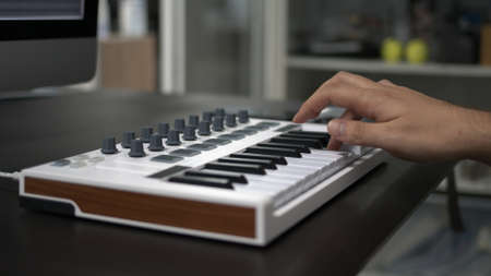Male hand playing electronic keyboard, midi keys on the table. Right male hands with midi keyboard with keys and pads, closeup shot