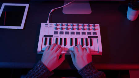 Closeup of hands composing music in night using midi controller. Top view of person playing music with electronic keyboard, midi keys on the table with neon lights Stock fotó