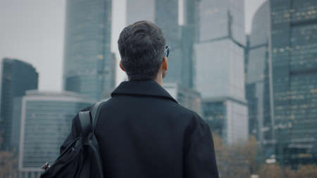 Man in coat looking at the skyscrapers pan shot right to left. Gimbal back shot of businessman in eyeglasses near skyscrapers in business city Stock fotó