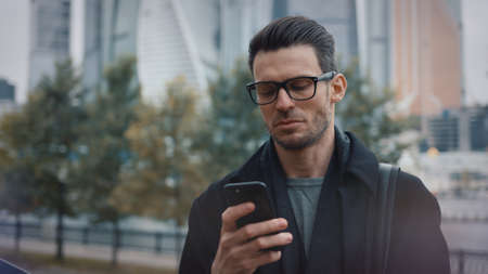 Man in black coat and eyeglasses with phone walking on background of business skyscrapers in Moscow, slow motion. Portrait shot of young man in the city business area
