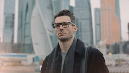 Man in eyeglasses on background of business skyscrapers, looking at the camera. Middle shot of businessman in coat standing near international business centre in moscow