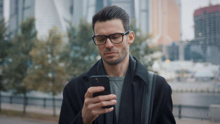Man in black coat and eyeglasses with phone walking on background of business skyscrapers in Moscow, slow motion. Middle shot of young man in the city business area