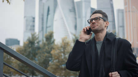 Man with phone talking on background of business skyscrapers in autumn. Man in coat and eyeglasses smiling standing and chatting on the phone in business area, cloudy day