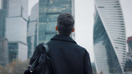 Man in black coat going towards business city skyscrapers in the evening, slow motion, lights in the windows. Gimbal shot of young businessman, no face, with bag Stock fotó