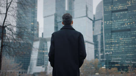 Man in black coat going towards business city skyscrapers in the evening, slow motion, lights in the windows. Gimbal shot of young businessman, no face Stock fotó