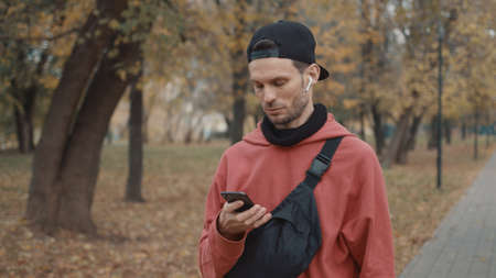 Man in cap and earbuds standing with phone in the park with yellow leaves. Male in red hoodie, sportswear typing in the phone, gimbal shot Stock fotó