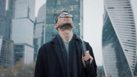 Man in coat looking up to the sky on background of skyscrapers pan shot right to left. Gimbal shot of businessman in eyeglasses near skyscrapers in business city