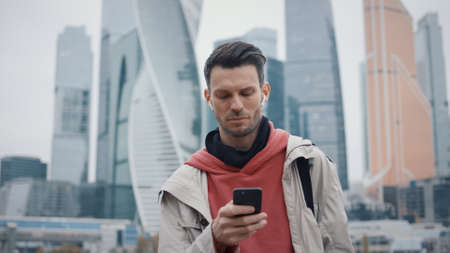Man with phone on background of business skyscrapers in business city, autumn cloudy day. Young man in beige coat looking at the phone smiling, middle shot