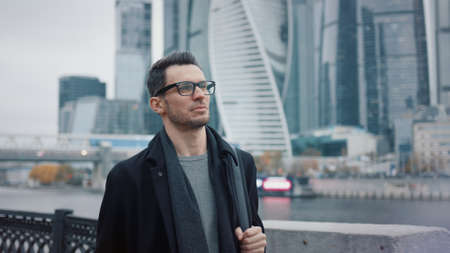 Man in black coat and eyeglasses walking on background of business skyscrapers in Moscow, slow motion. Middle shot of young man in the city business area