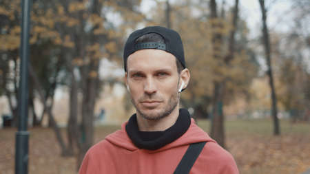Man in cap and earbuds standing in the park with yellow leaves. Male in red hoodie, sportswear looking at the camera in the city park alone, gimbal shot