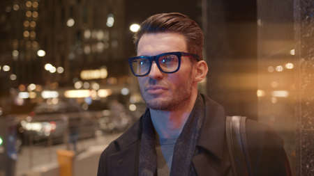 Man in eyeglasses standing on background of business skyscrapers, windows with lights. Portrait gimbal shot of businessman in coat standing near business centre downtown at night