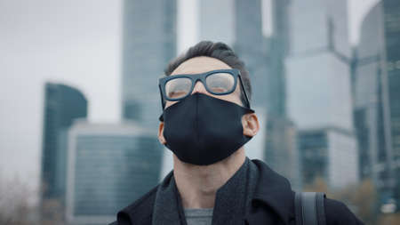 Man in eyeglasses and protective mask on background of business skyscrapers, looking up to the sky. Gimbal pan shot of businessman in coat standing near international business centre