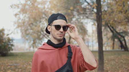 Man runner put off eyeglasses and put on earbuds getting ready for run in a city park. Runner in red hoodie wearing black cap, getting ready for jogging, gimbal shot
