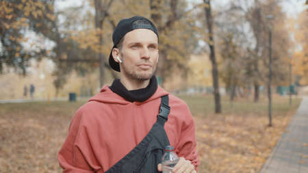Man runner closeup in red hoodie and earbuds drinking water in the park slow motion, on background of yellow trees. Gimbal shot of man drinking water from the bottle