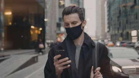 Man outdoors wearing a black protective mask, looking at the phone. Man in black clothes standing on background of city buildings and road with cars