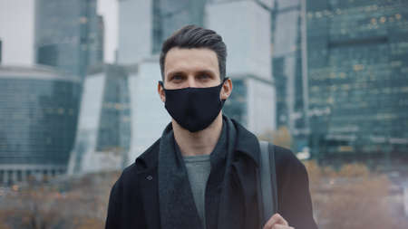 Man in black coat and black protective mask on background of business skyscrapers, looking at the camera. Gimbal shot of businessman in coat standing near international business centre