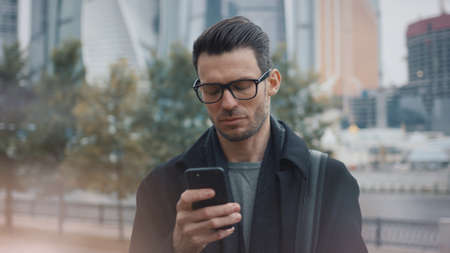 Man in black coat and eyeglasses with phone walking on background of business skyscrapers in Moscow, slow motion. Middle shot of young man in the city business area Stock fotó