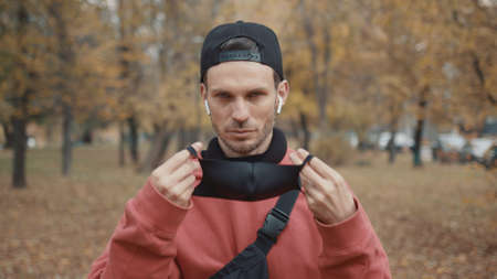 Man walking in the park putting on black protective mask, male in black cap wearing red hoodie. Gimbal shot of young man on the walk in the park along yellow trees Stock fotó