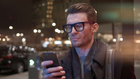 Man in eyeglasses with phone in hand on background of building with lights on. Gimbal night shot of caucasian man texting in phone near business building with cars