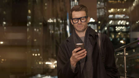 Man in eyeglasses with phone in hand on background of building with lights on. Handheld night shot of caucasian man texting in phone near business building with cars