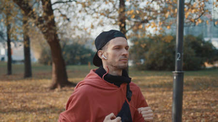 Man running in the park, young man in sport clothes and cap listening to music running through the park in the autumn day, middle shot, jogging concept
