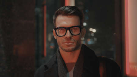 Man in eyeglasses looking at the camera with red lights on face, night time. Portrait shot of serious businessman outside on background of glass window