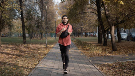 Man running in the park slow motion, young man in sport clothes and cap listening to music running through the park in the autumn day. Front view Stock fotó