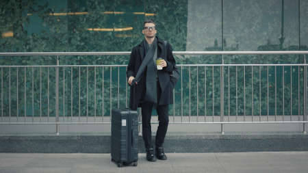 Man in black coat stand and wait for a taxi on background of airport terminal, with suitcase near road. Businessman traveller drinking coffee near road in windy weather Stock fotó