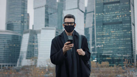 Man in black coat, eyeglasses and black protective mask walking on background of business skyscrapers in Moscow, slow motion. Middle shot of young man in the city business area