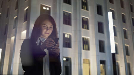 Woman at night with phone wearing black jacket and neck scarf, on background of blue buildings. Middle shot of young woman alone texting in the phone, night shot Stock fotó