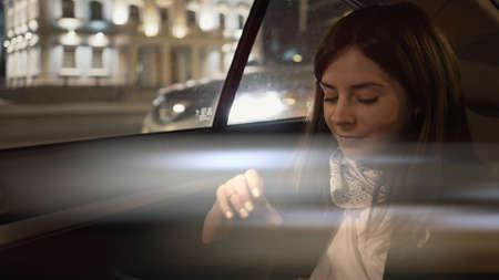 Young woman smiling sitting in car backseat with phone in hands, city lights on background. Delightful female passenger in black jacket and neck scarf alone with phone, in car late at night
