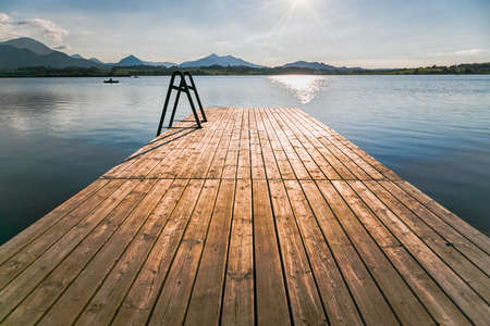 Hopfensee with wooden landing stage, in the background the Alp Mountains, Allgäu, Bavaria, Germany