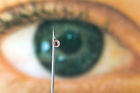 The eye of a doctor looking at a droplet on a syringe photo