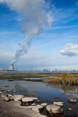 cooling towers of a nuclear power plant creating clouds in the Antwerp harbor Stock Photo - 5750460