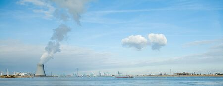 cooling towers of a nuclear power plant creating clouds in the Antwerp harbor Stock Photo - 5756304