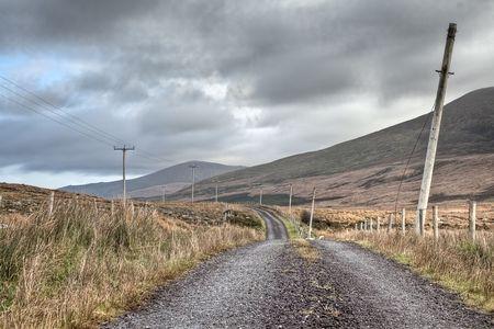 curving: dirty road curving trough Irish hills under a dark cloudy sky