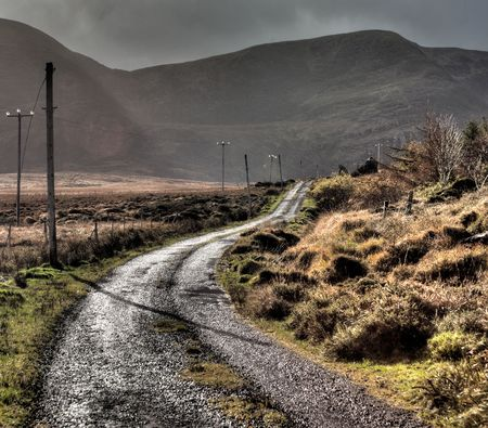 curving: road curving trough Irish hills with rays of sun reflecting on the wet asphalt Stock Photo