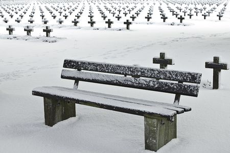 bench at graveyard surrounded with crosses and covered in snow photo