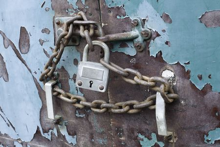 lock and chain on an old weathered blue door Stock Photo - 6178102