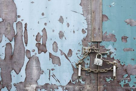 lock and chain on an old weathered blue door photo