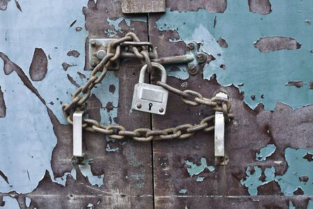 lock and chain on an old weathered blue door Stock Photo - 6178105
